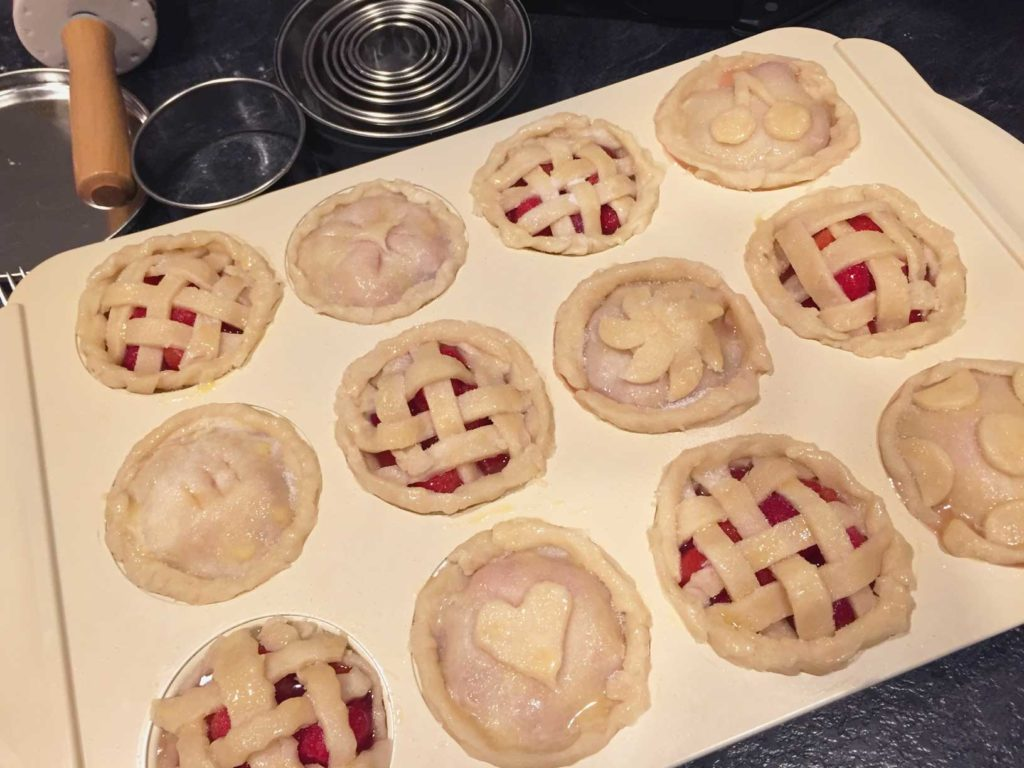 Overhead view of the mini pies, decorated with dough, ready to go in the oven