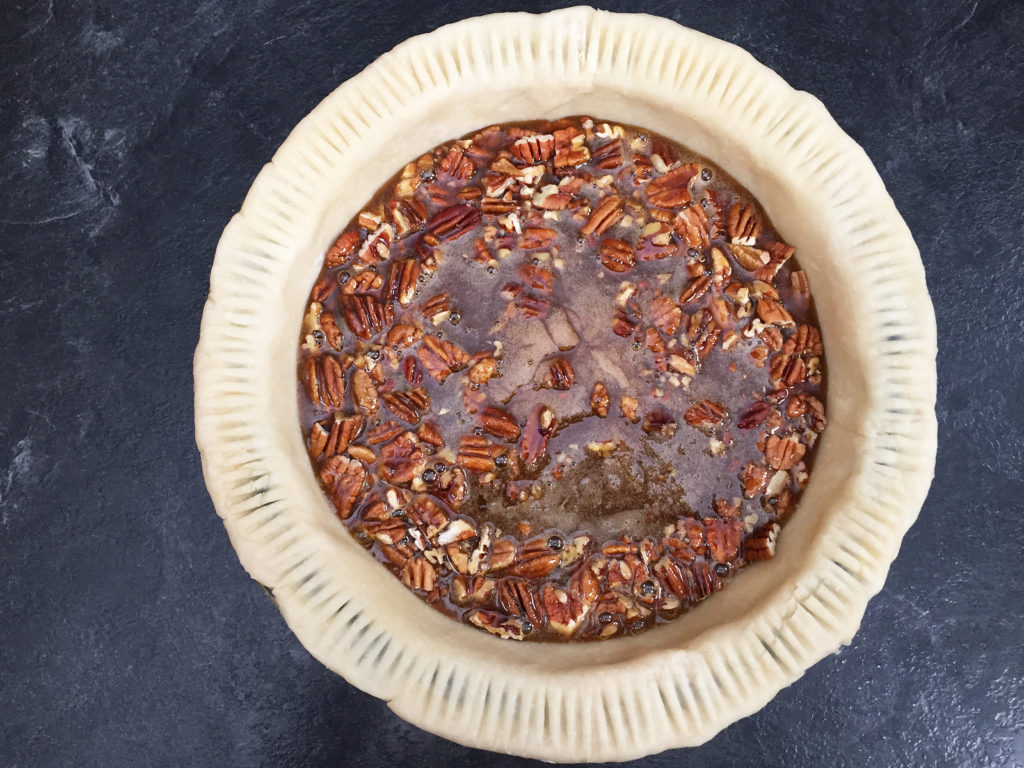 pouring filling into pecan pie crust