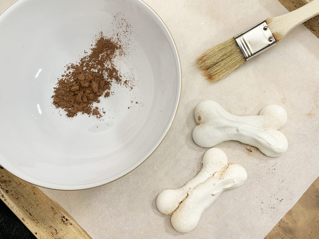 brushing meringue bones with cocoa powder
