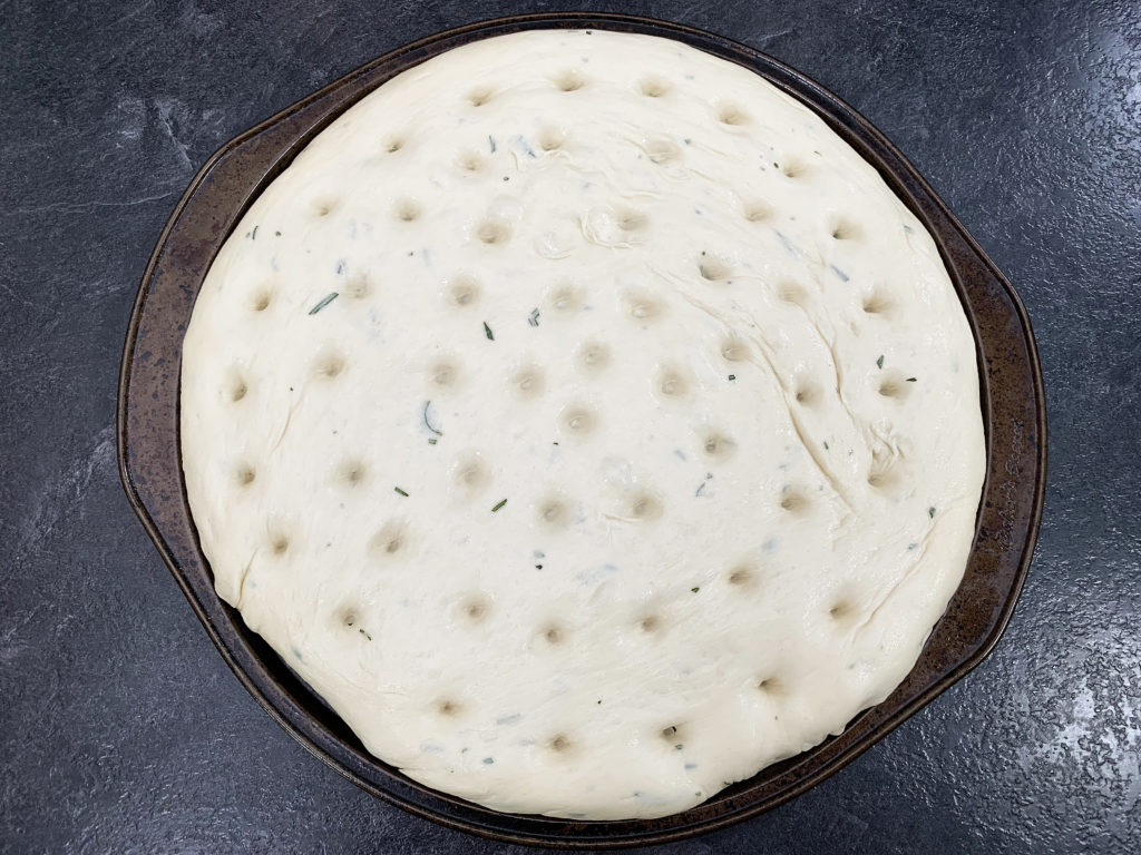 focaccia dough in a pan with holes poked in and drizzled with olive oil