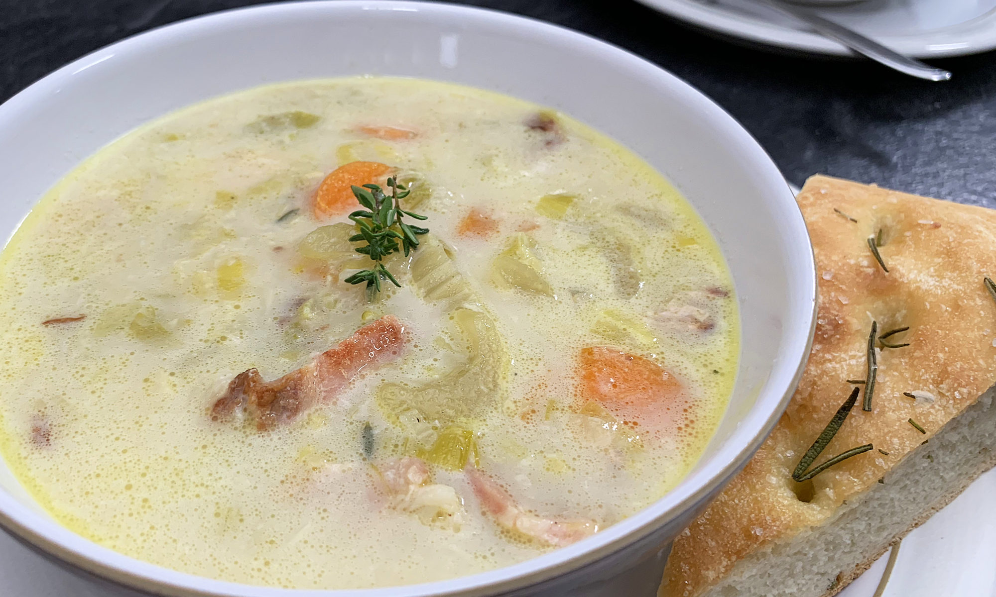 bowl of creamy potato bacon leek soup with focaccia bread