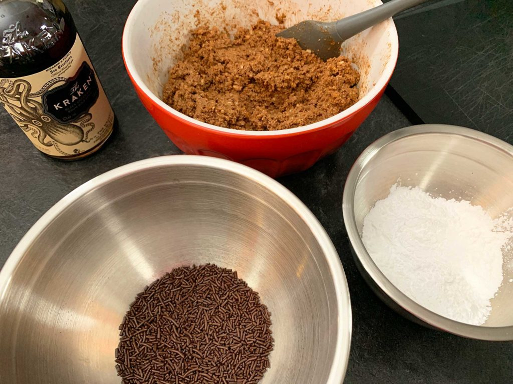 bowl of rum ball mixture beside a bowl of chocolate sprinkles and a bowl of icing sugar