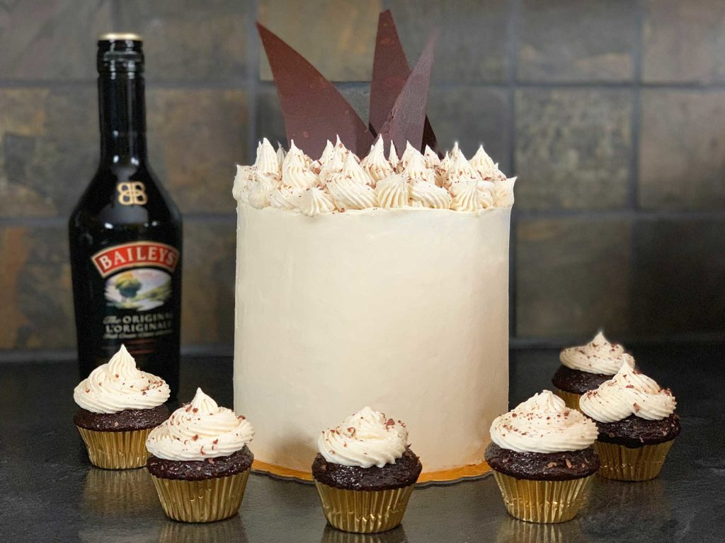 baileys chocolate cake surrounded by cupcakes