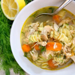 bowl of chicken noodle soup with lemon and fresh dill on the side