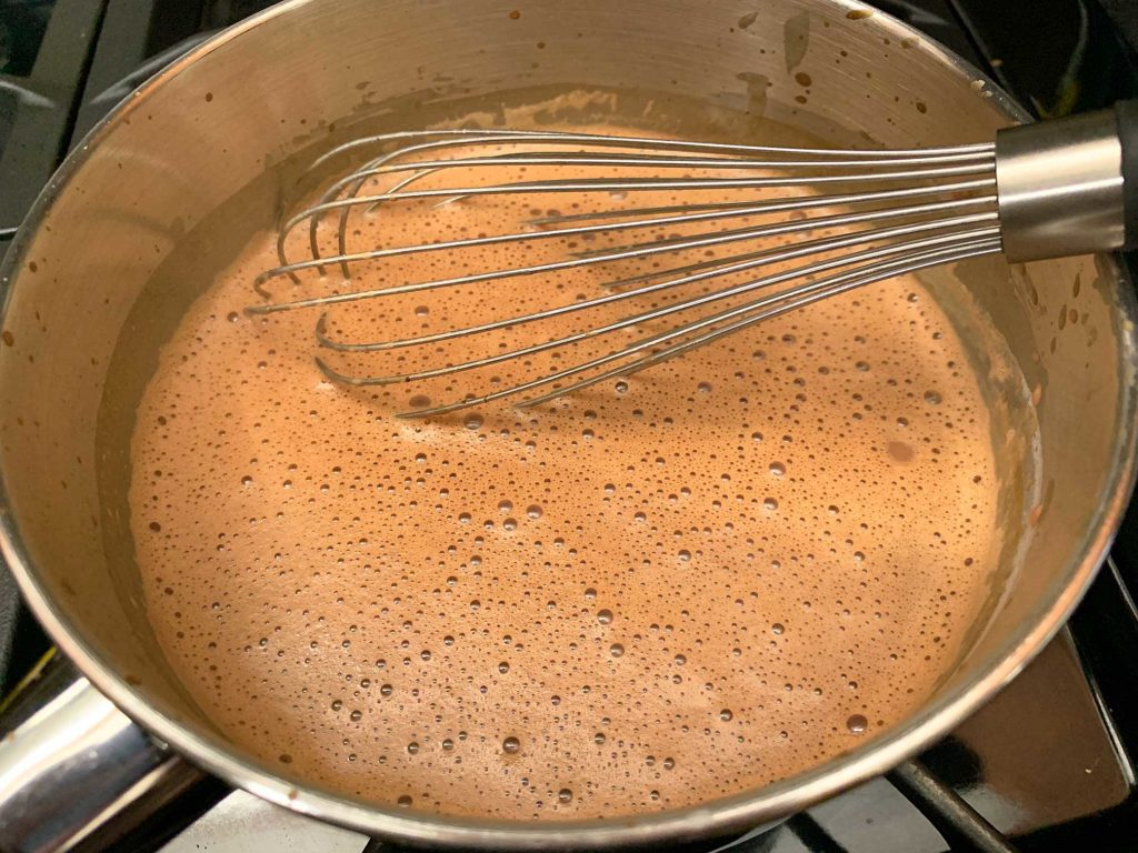 whisking the melted chocolate into the hot milk