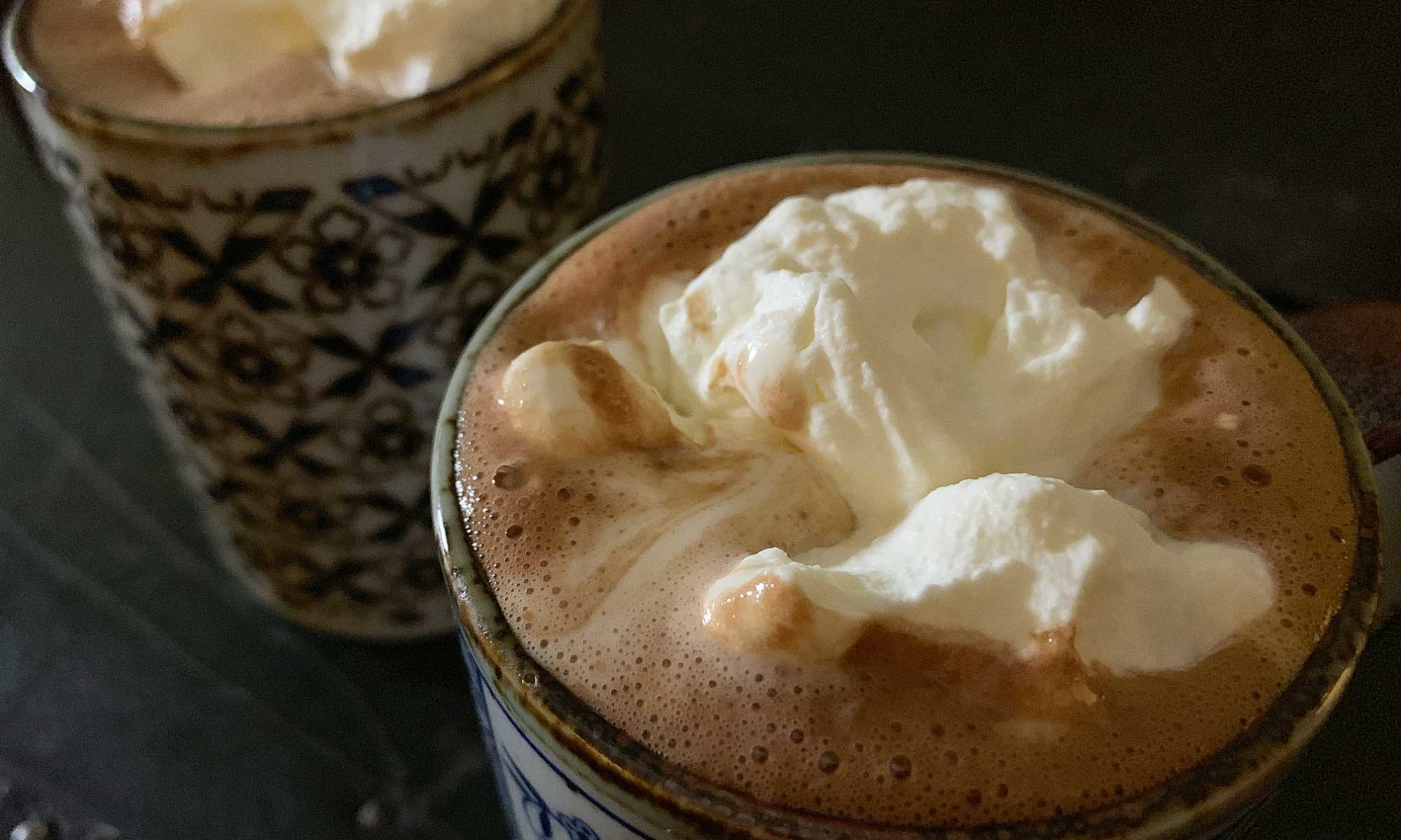 hot chocolate in mugs, topped with whipped cream