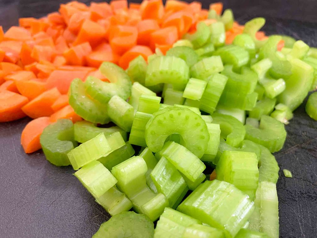 chopped up celery and carrot on a cutting board