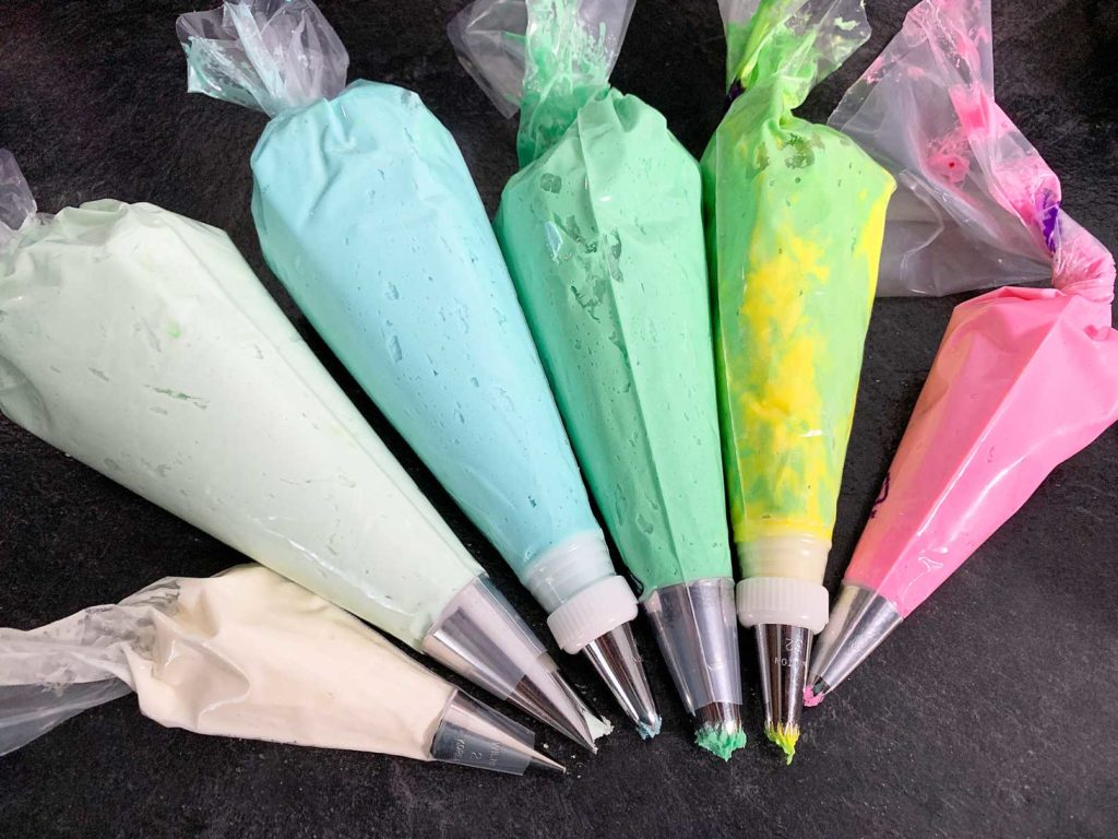 piping bags filled with buttercream in assorted colours