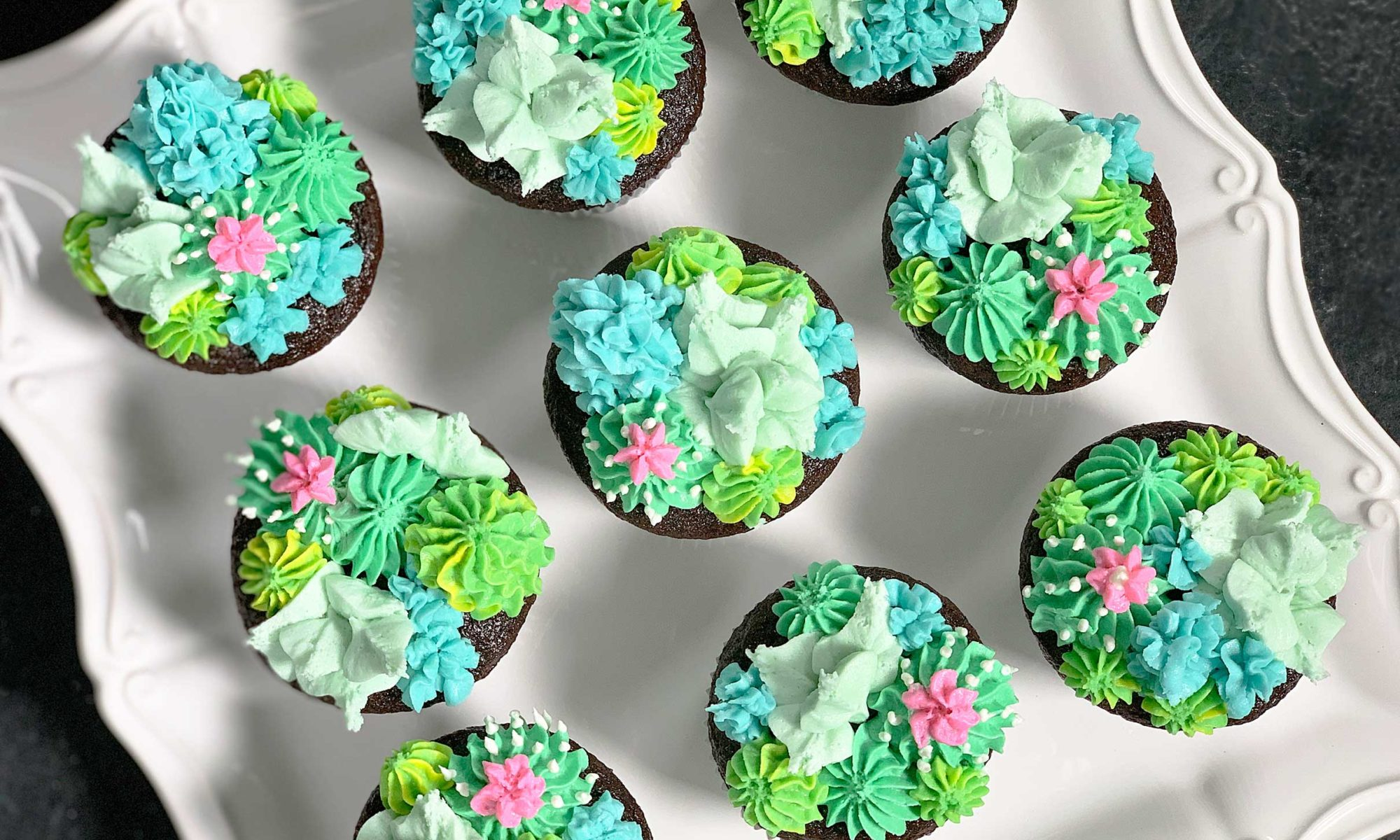overhead view of cupcakes with buttercream cacti and succulents