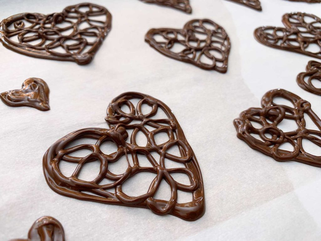 Decorative chocolate hearts on a sheet of parchment paper