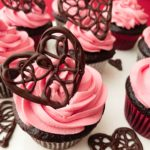Close up of chocolate cupcakes with raspberry buttercream, with a decorate chocolate heart on top