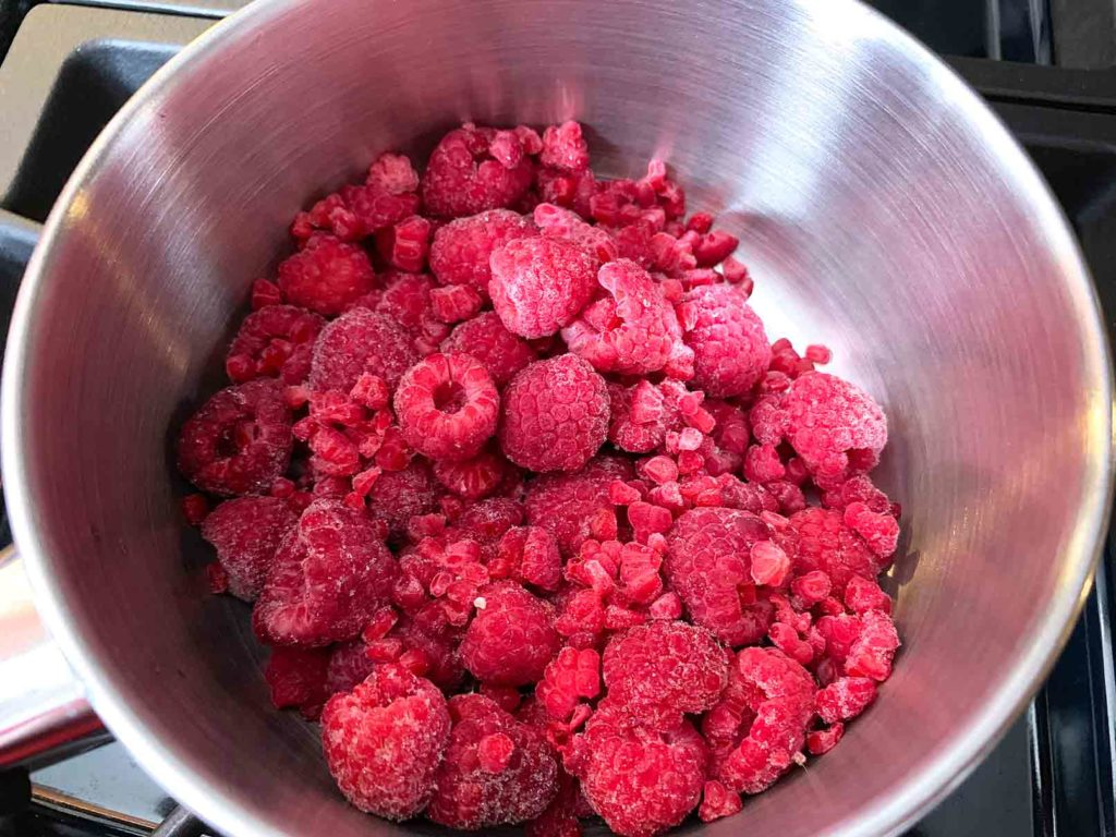 Frozen raspberries in a small saucepan