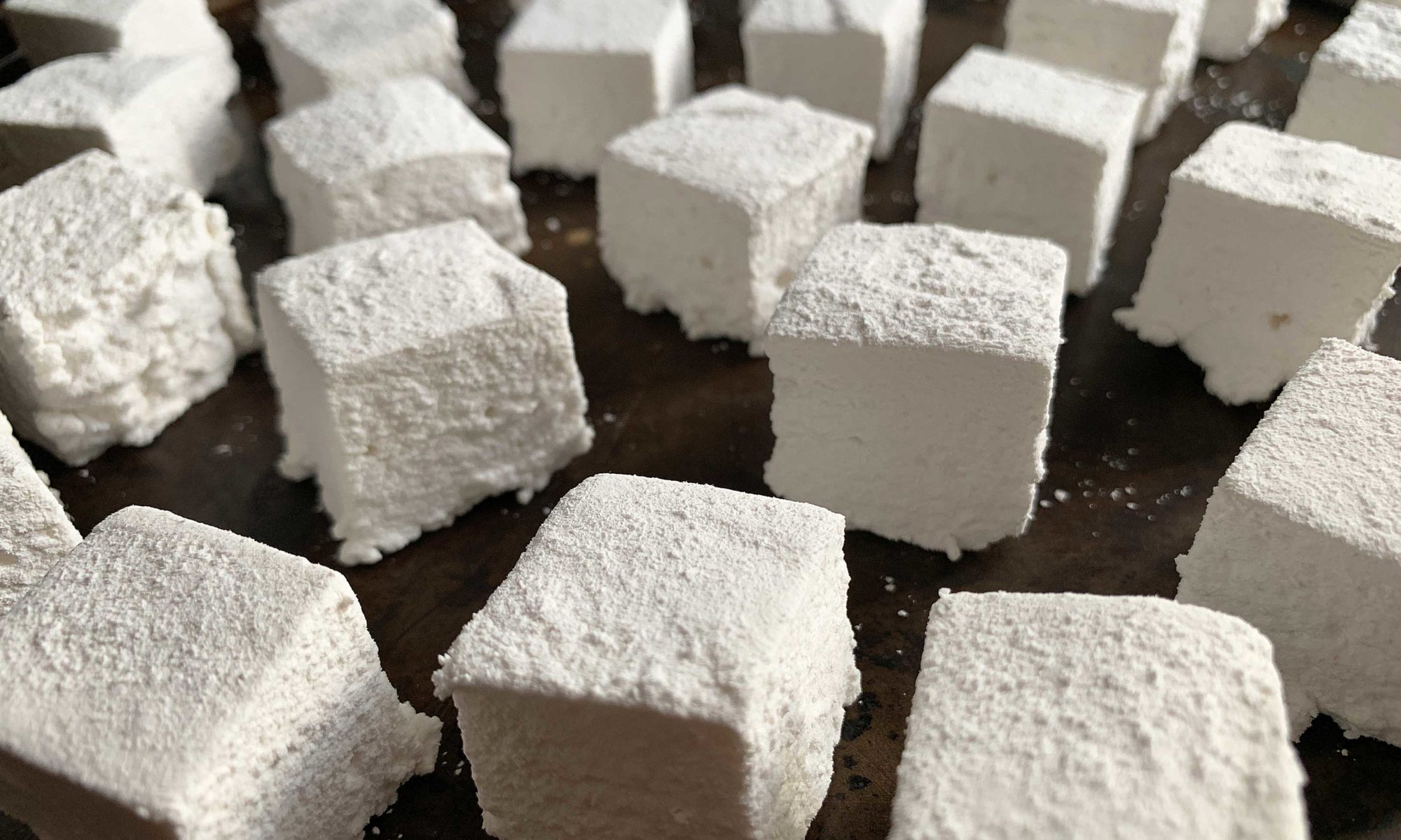 Close up shot of a pan full of homemade marshmallows, cut into cubes