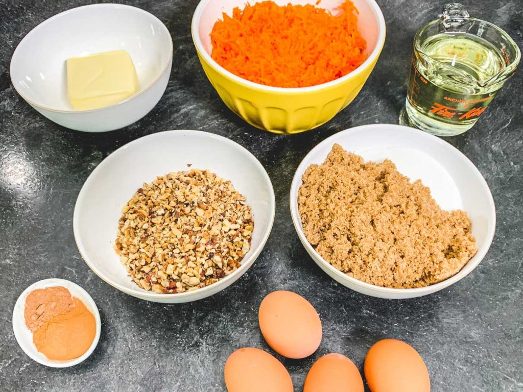 ingredients for carrot cake, measured out in separate bowls