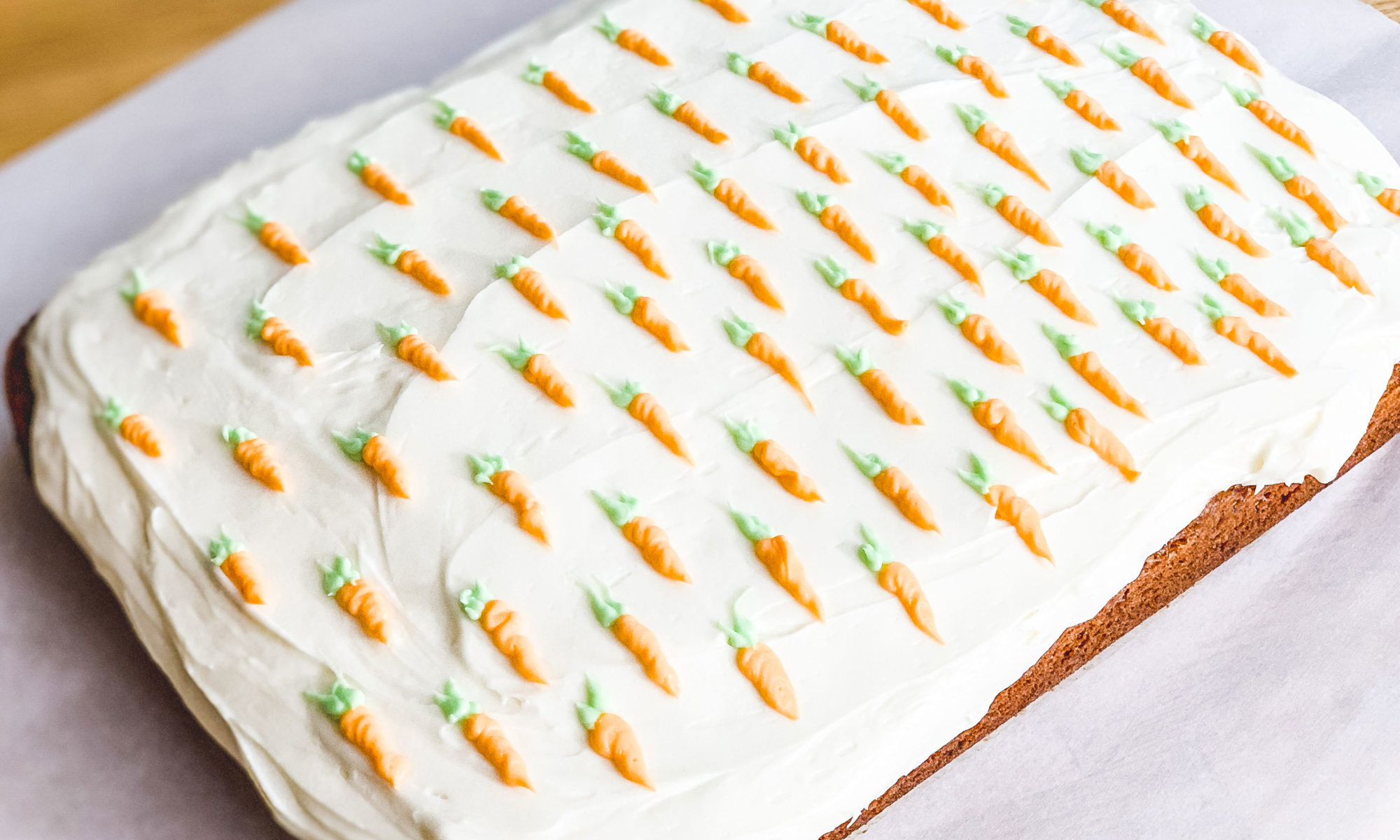 frosted carrot cake, with tiny carrots piped on top