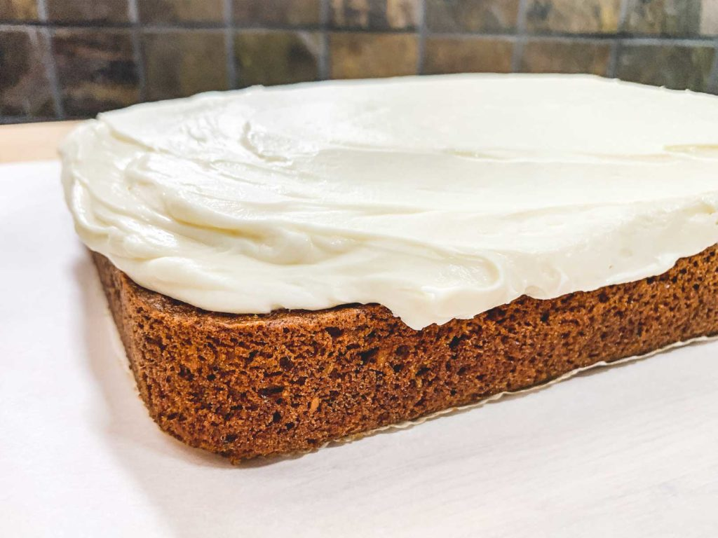 close up of cream cheese frosting spread on top of carrot cake