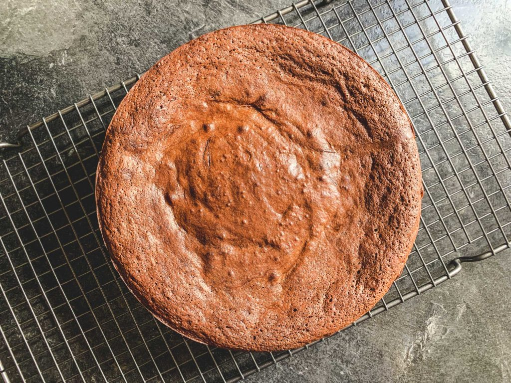 overhead shot of flourless chocolate cake on a cooling rack