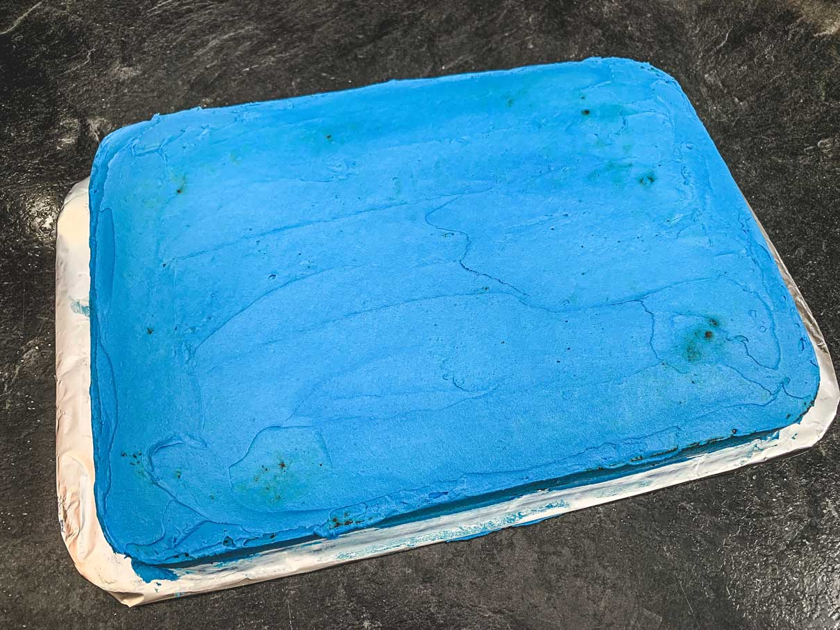 crumb coat of blue frosting on 9x13 cake
