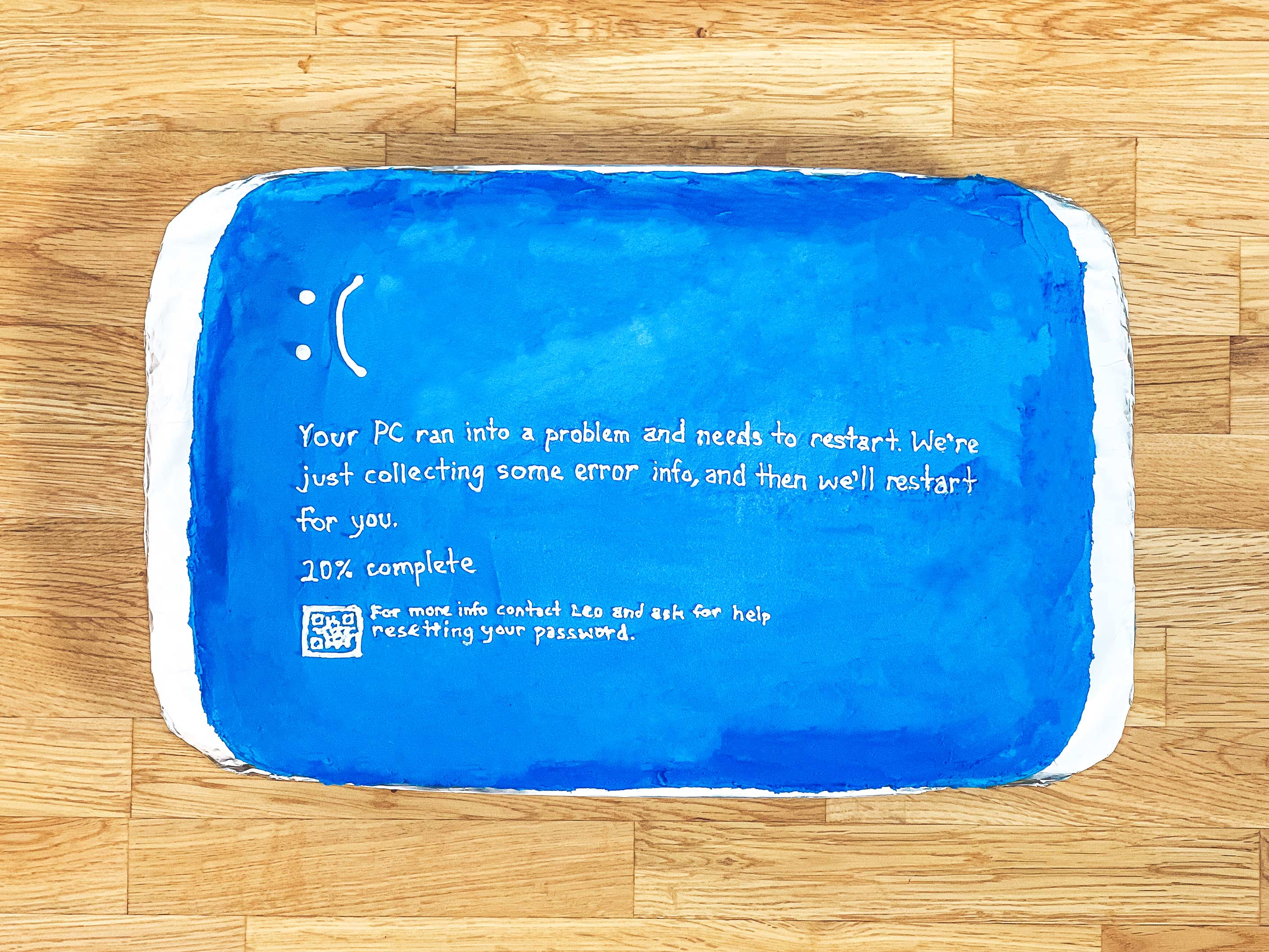 "blue cake with a sad face and writing on it saying ""Your PC ran into a problem and needs to restart. We're just collecting some error info, and then we'll restart for you. 20% complete."""