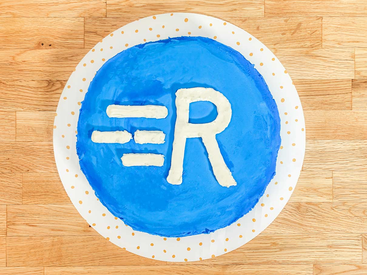 9 inch round cake with blue frosting and 'R' logo on it
