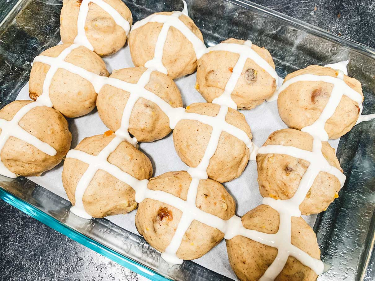 piping a cross on top of the risen dough buns