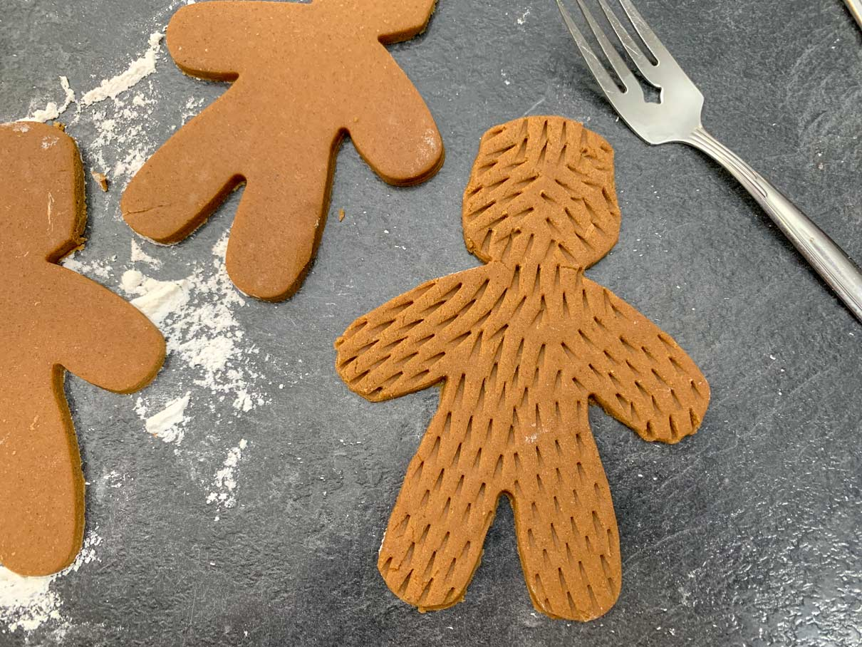 dough cut out into shape of gingerbread man, with indents pressed into surface from fork