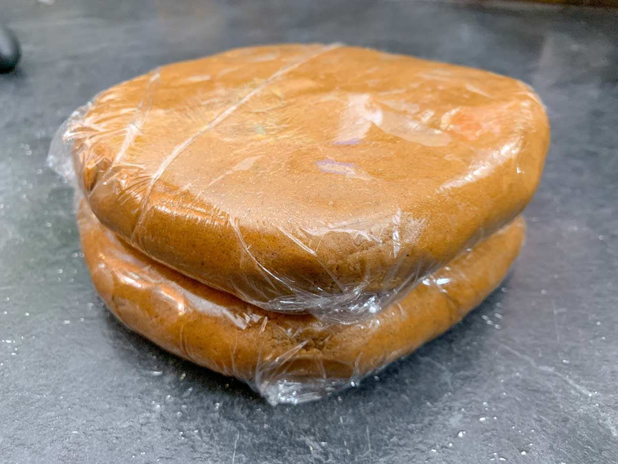 two discs of gingerbread dough, wrapped in plastic wrap, ready to go in fridge
