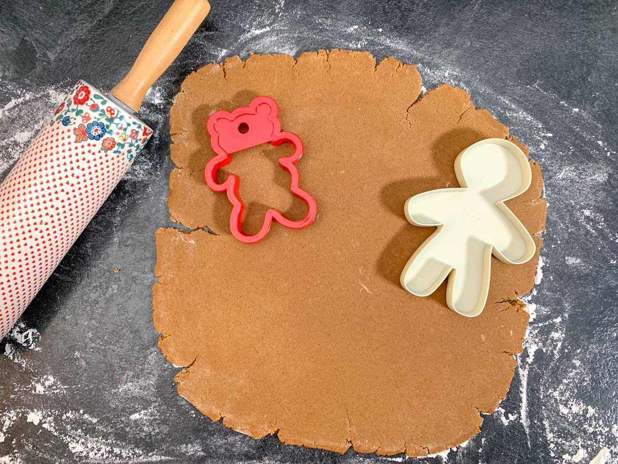 rolled out gingerbread dough with cookie cutters resting on top