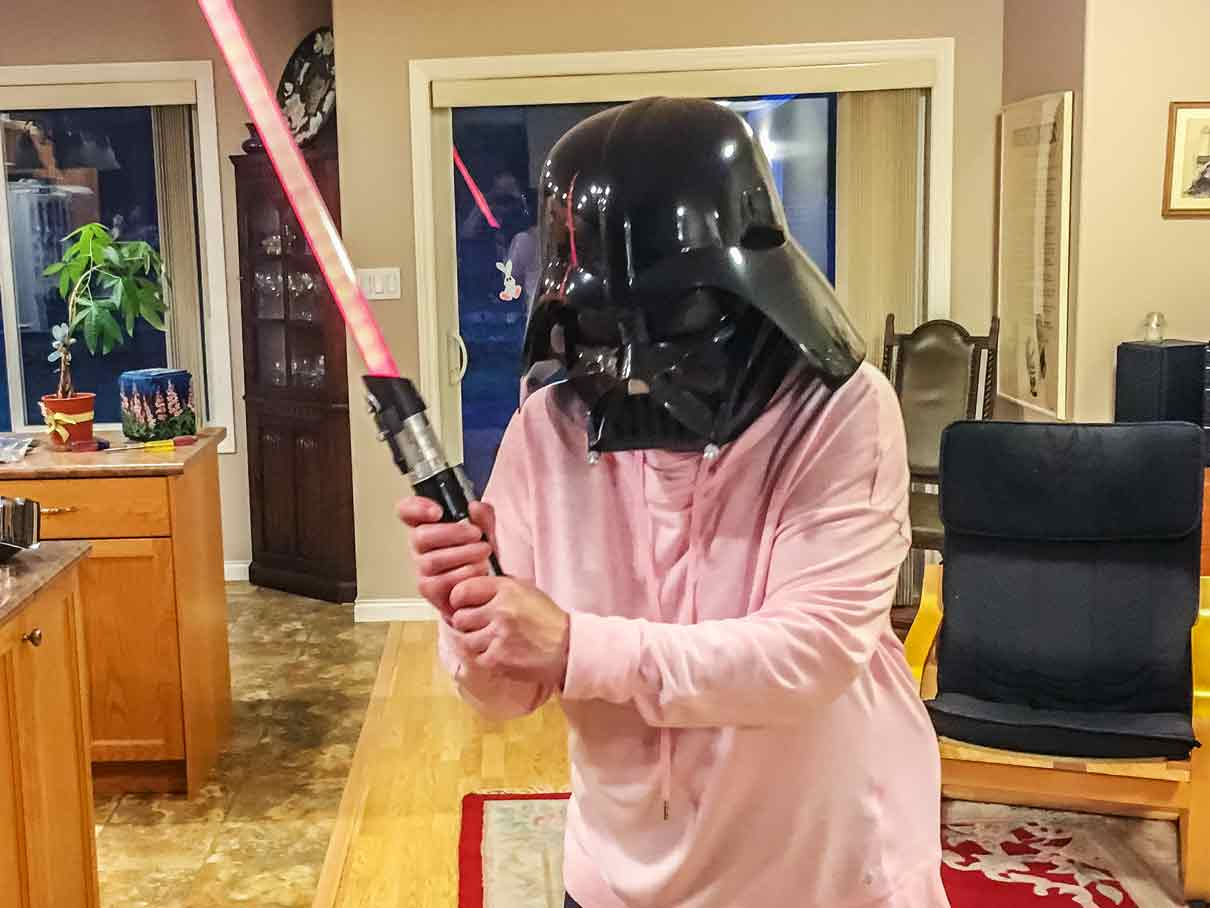 mom wearing Darth Vader helmet and holding light saber