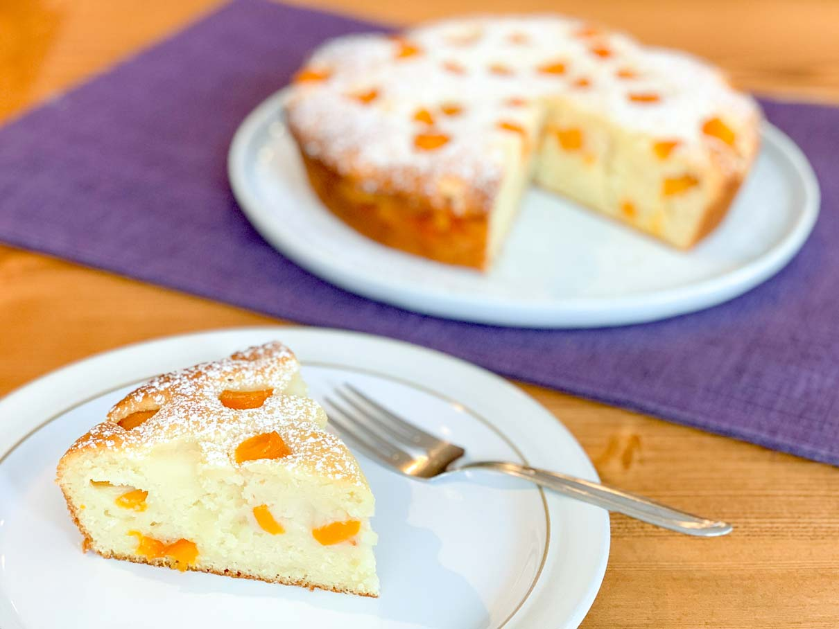 a slice of peach ricotta cake on a plate with the rest of the cake in the background