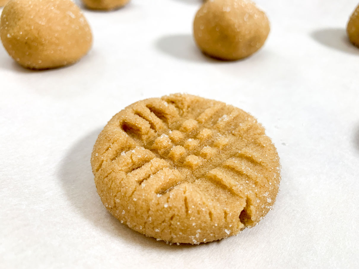 Peanut butter cookie dough ball with fork marks pressed into the surface