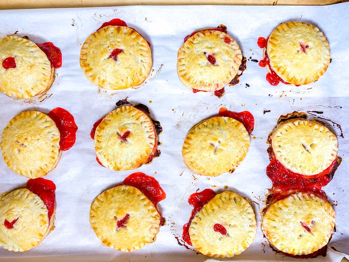 tray over freshly baked mini pies, many with the filling oozing out the sides