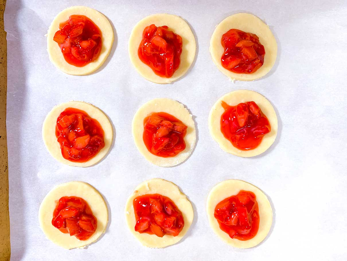 dough circles on a parchment lined tray, each with a spoonful of filling on top