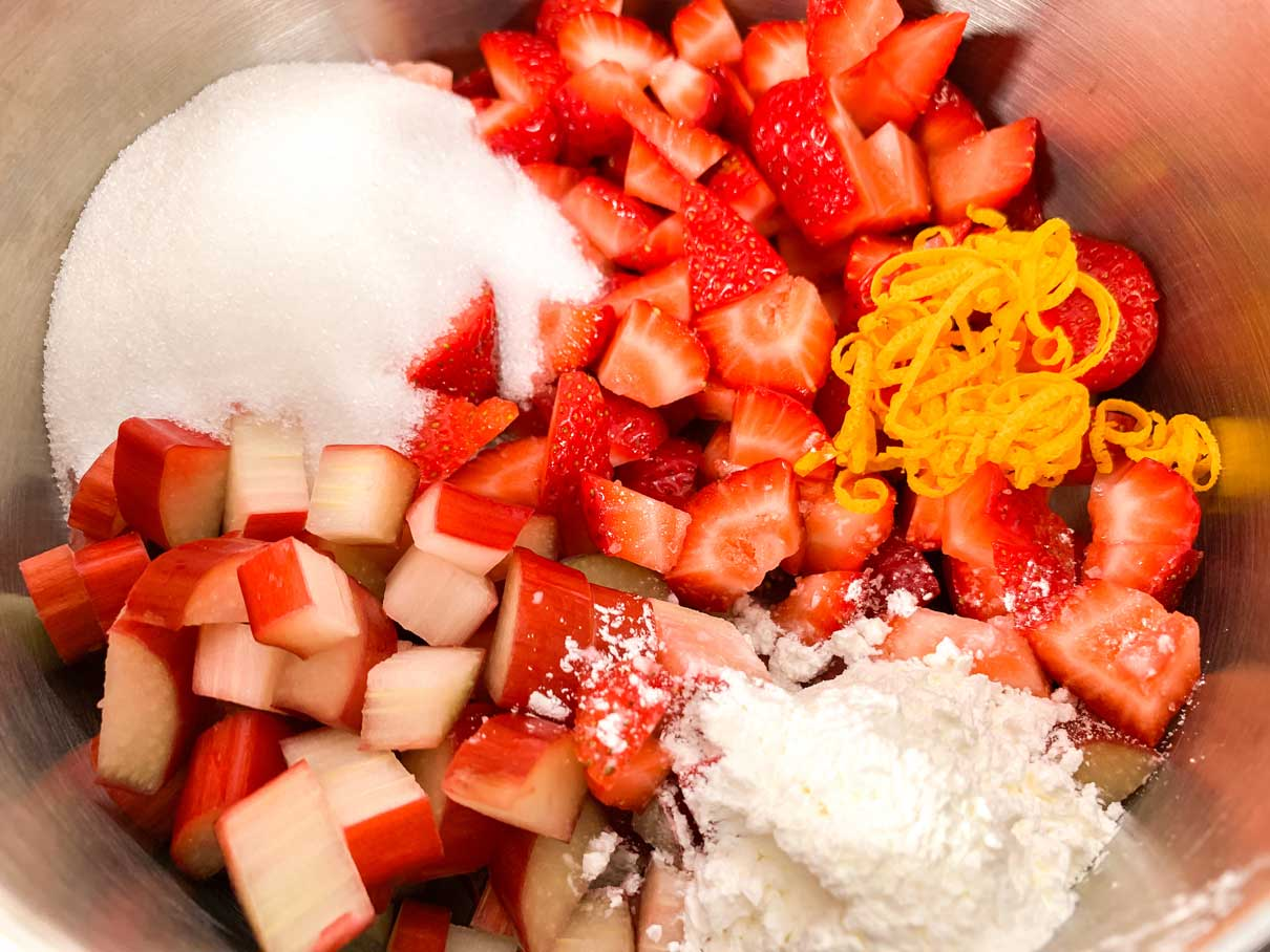 chopped up strawberries and rhubarb in a saucepan with sugar, cornstarch and orange zest