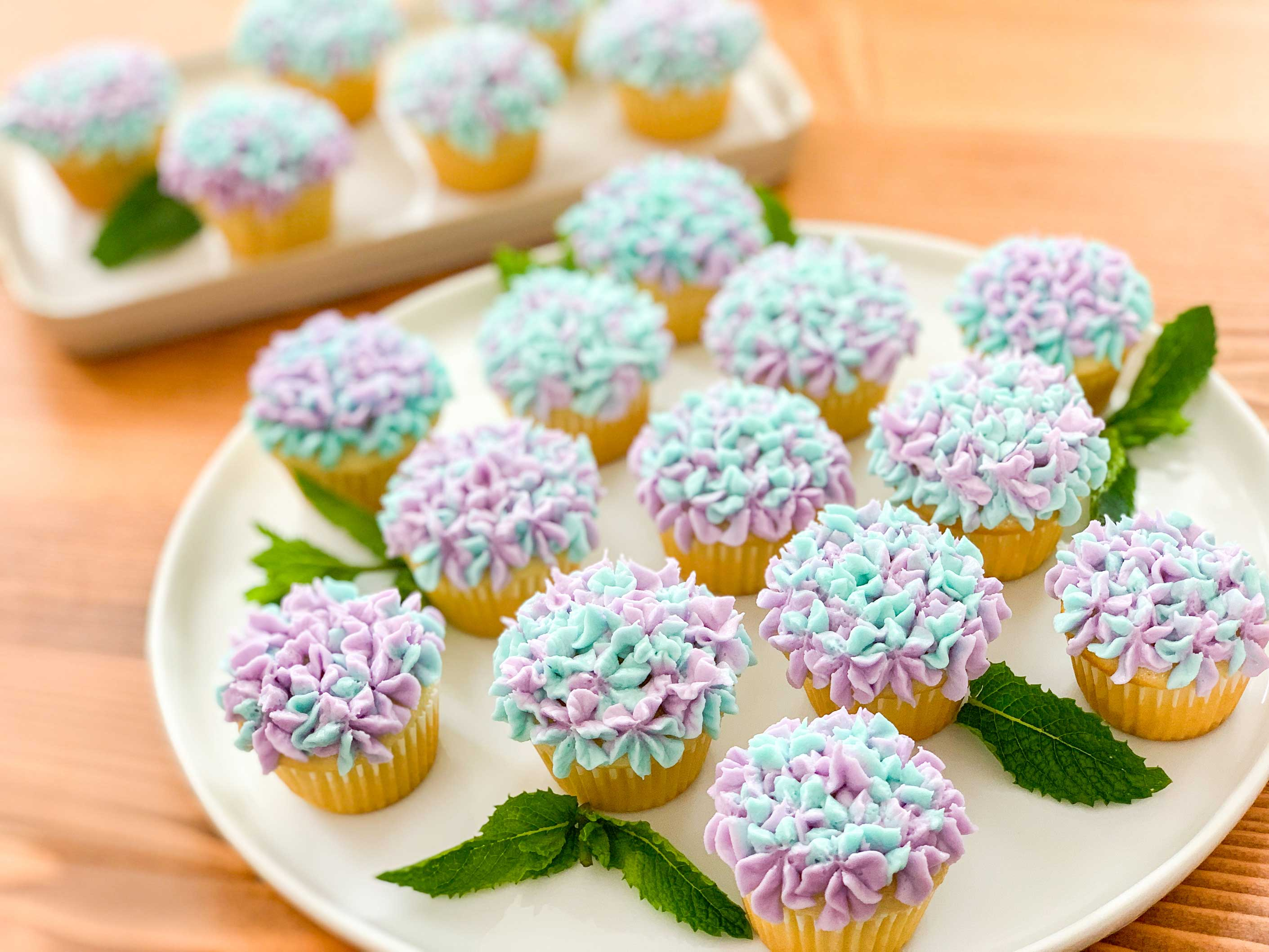 Mini hydrangea cupcakes on a round plate, accented with mint leaves
