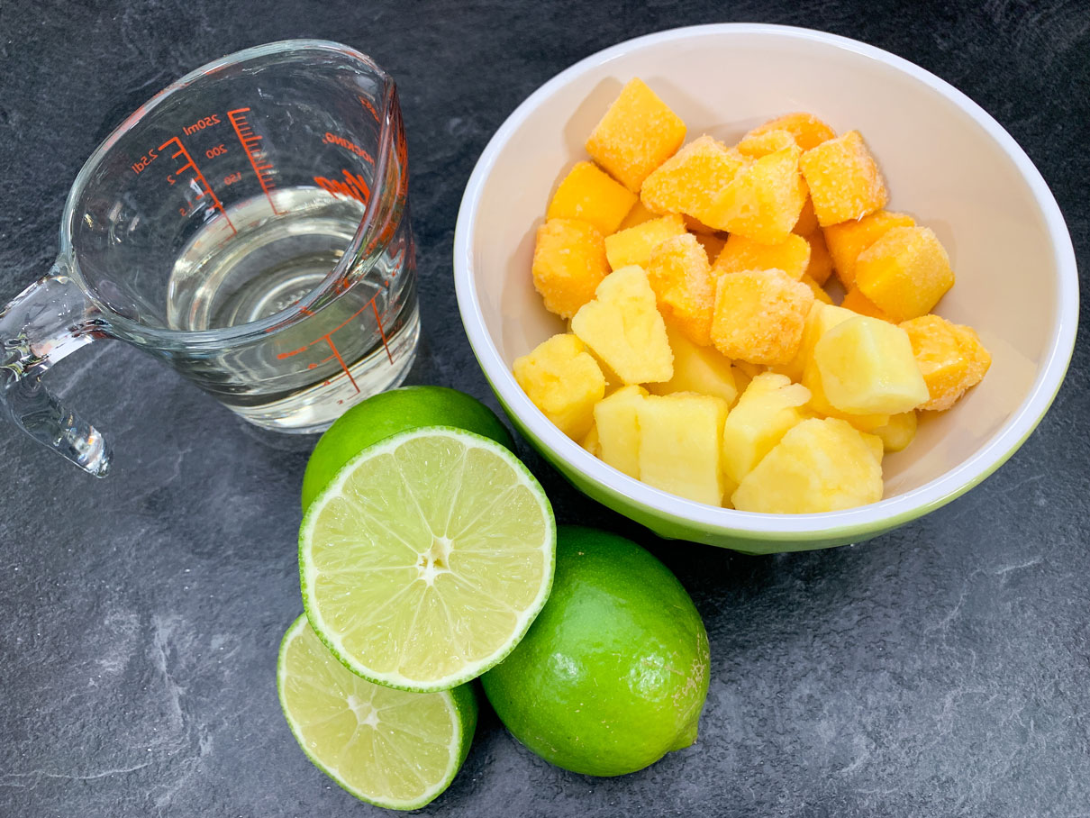 Frozen mango and pineapple in a bowl, next to some limes and tequila.