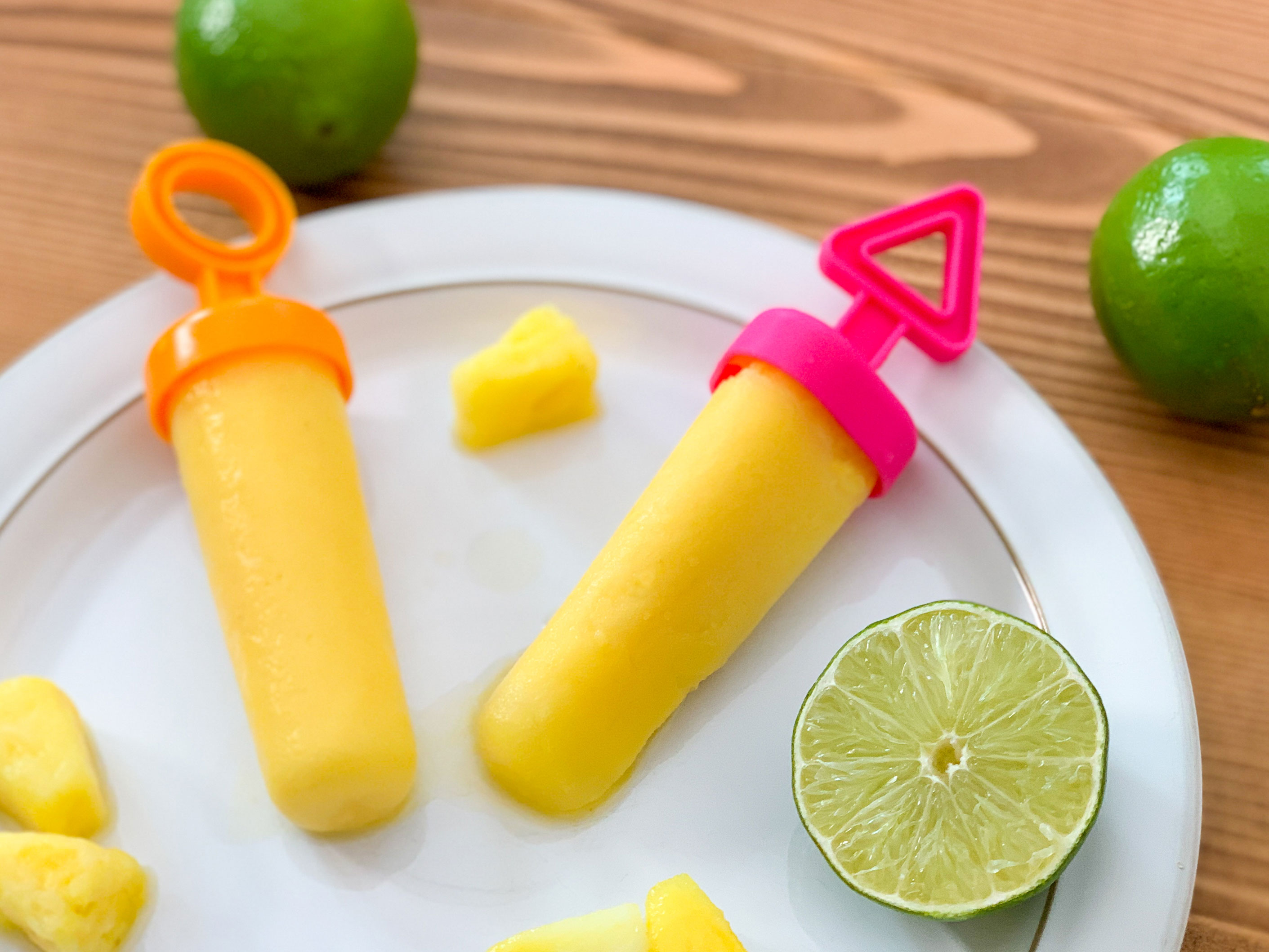 two frozen popsicles on a plate next to limes and pineapple pieces