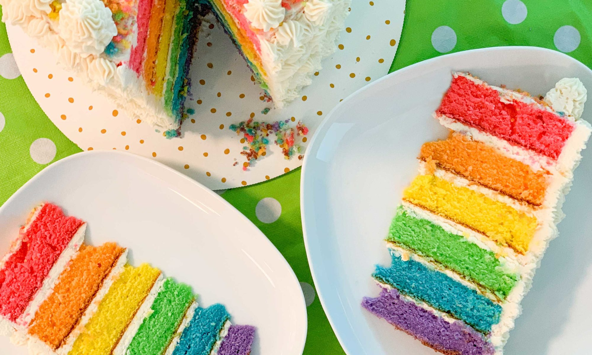overhead shot of the rainbow cake, with two slices cut out and on plates next to it