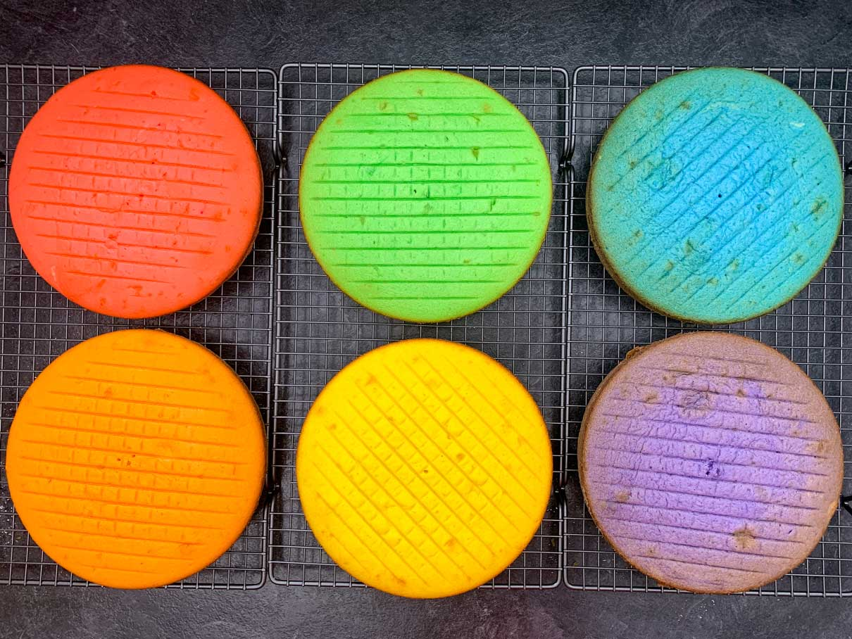 6 cakes baked and cooling on a wire rack (red, orange, yellow, green, blue and purple)