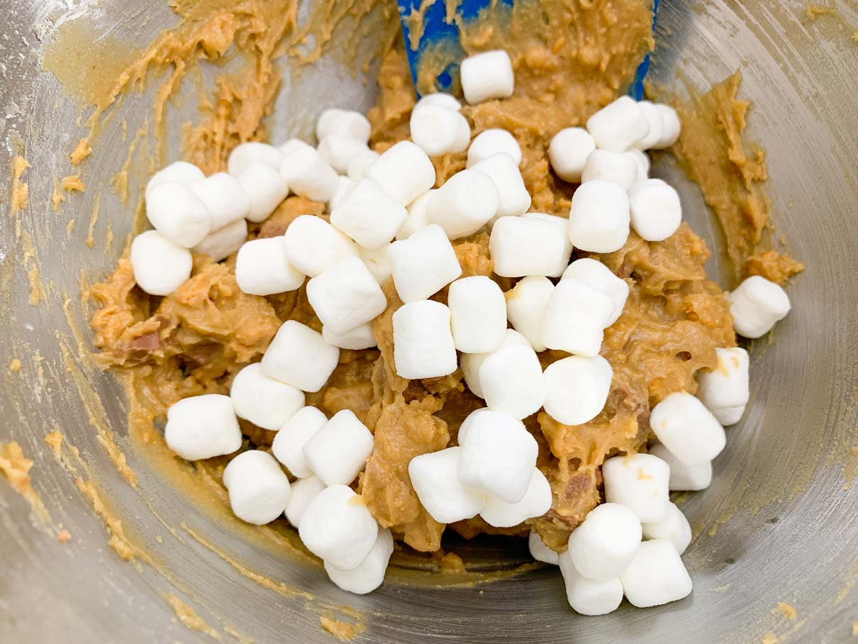 adding the marshmallows to the s'mores cookie dough
