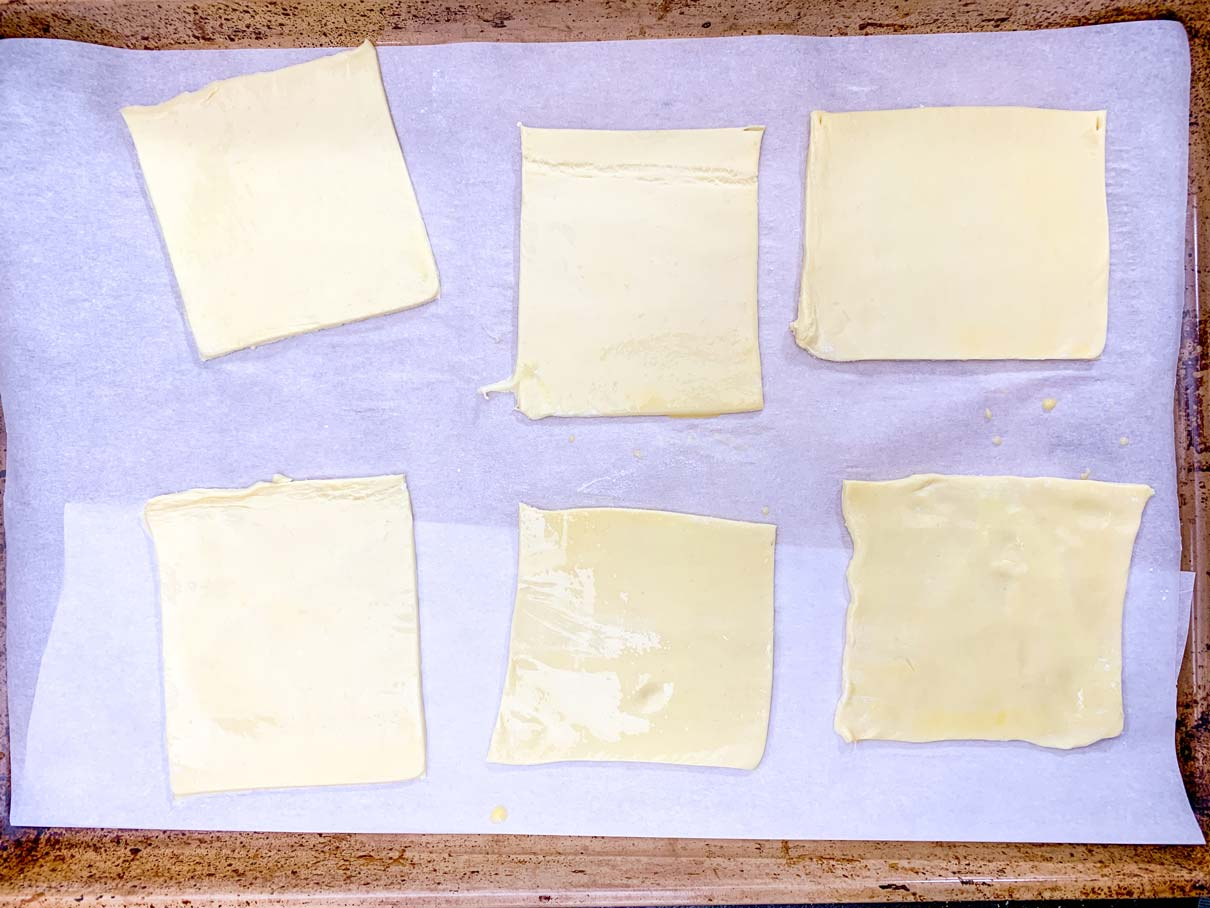 squares of puff pastry on a baking tray, brushed with egg wash