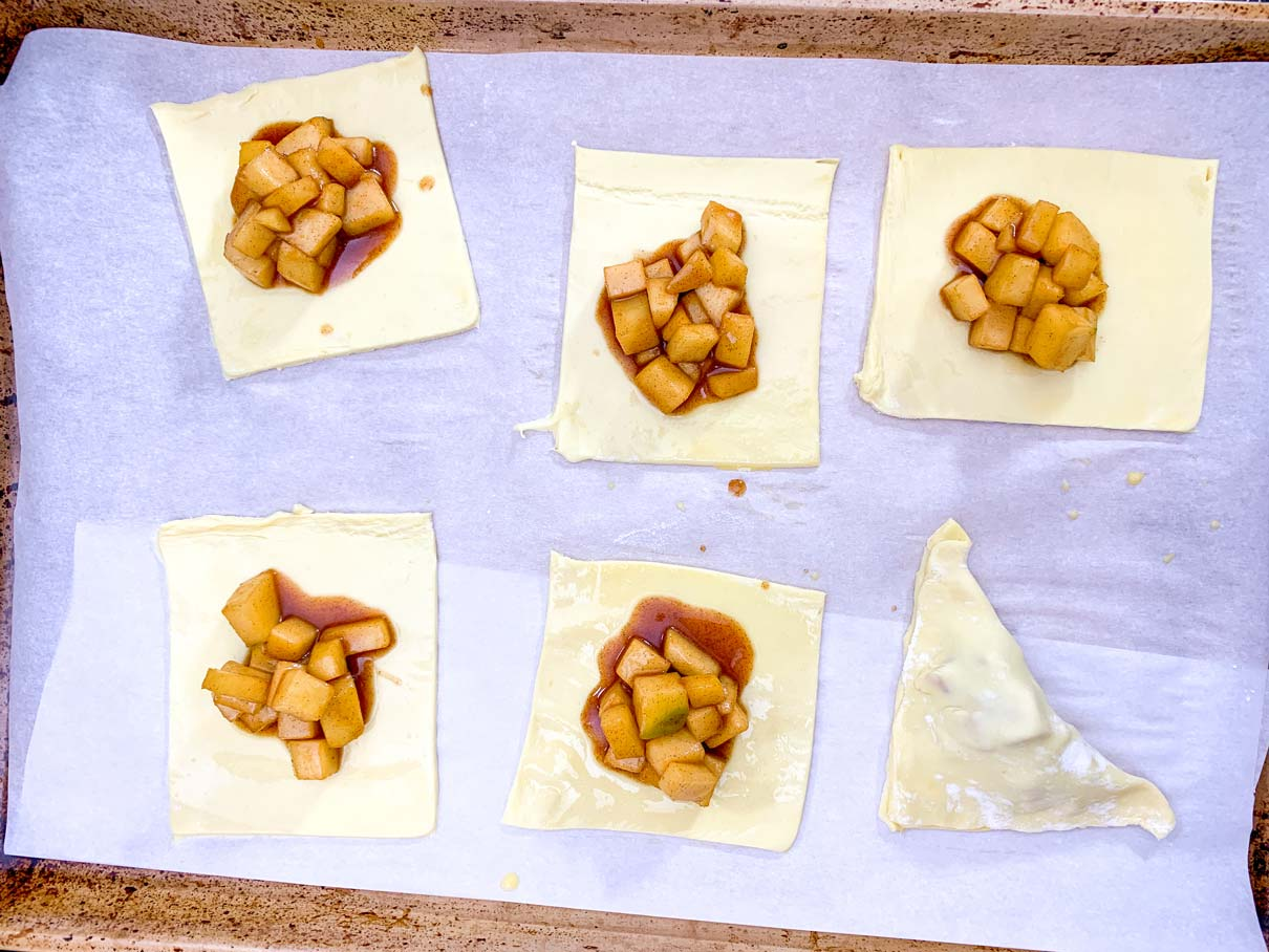 squares of puff pastry on a baking tray, with a spoonful of apple filling on top of each