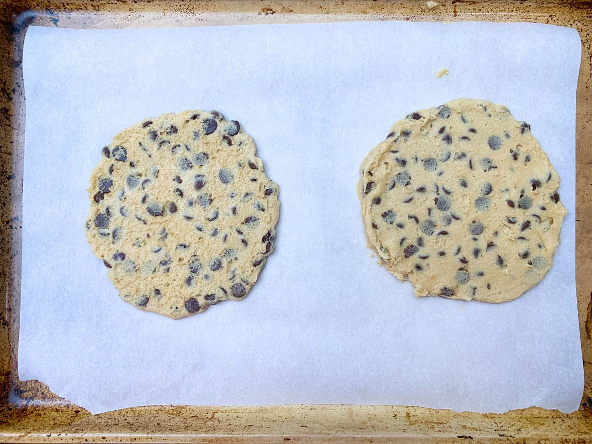to flattened piles of cookie dough on a baking tray, ready to go in the oven