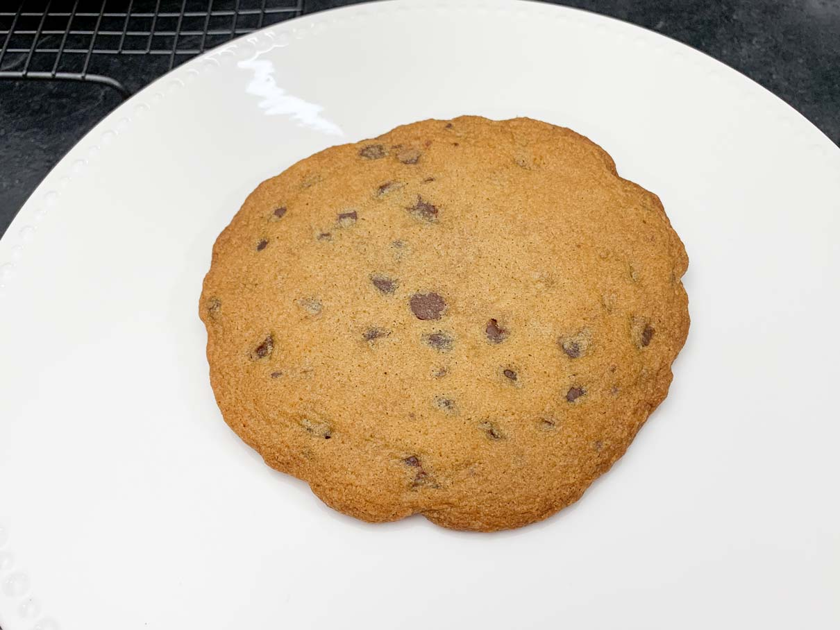 a chocolate chip cookie, resting on a cake plate, ready to be frosted