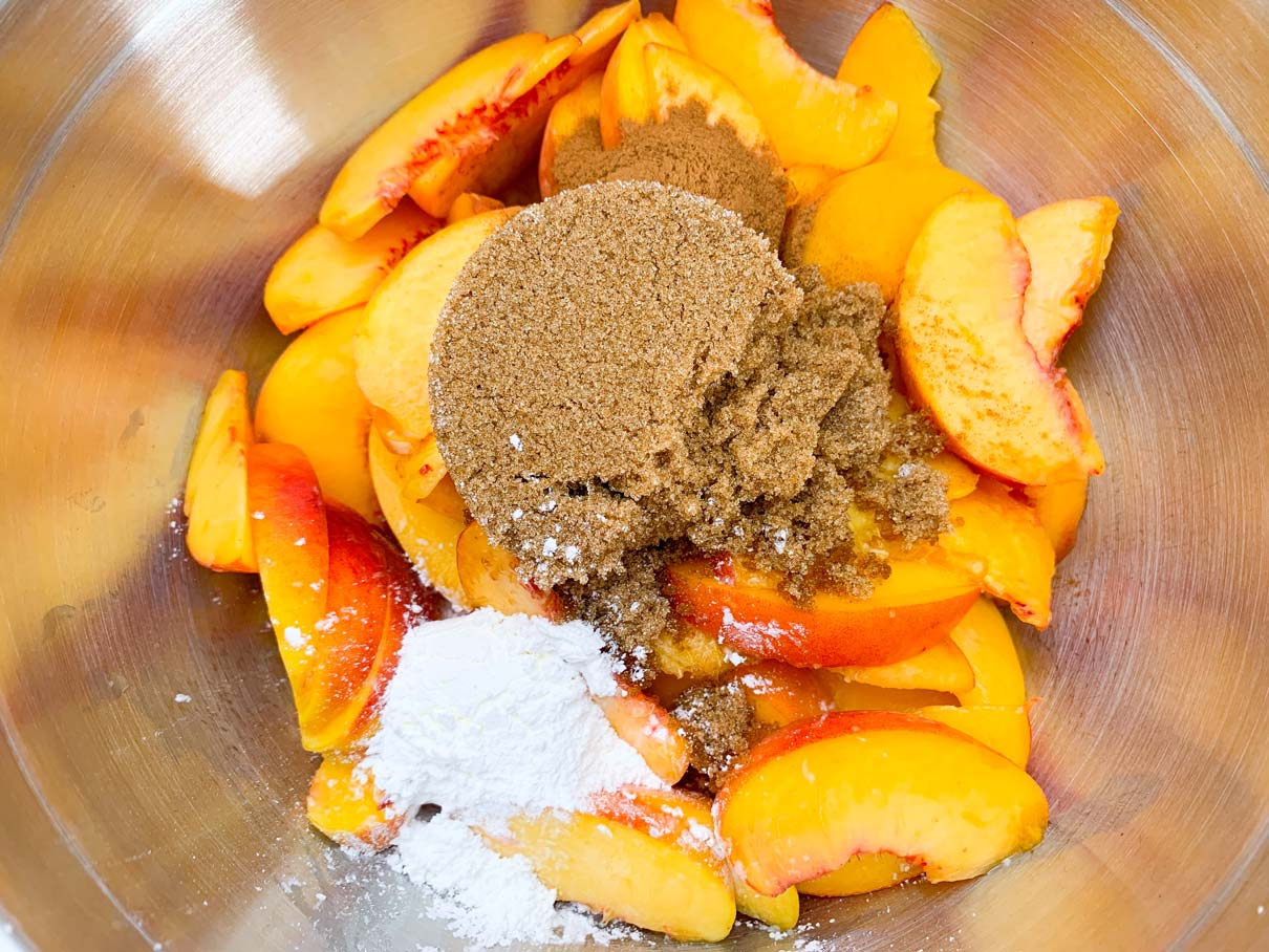 Fresh peaches, sliced up in a bowl with brown sugar, cinnamon and cornstarch sprinkled on top