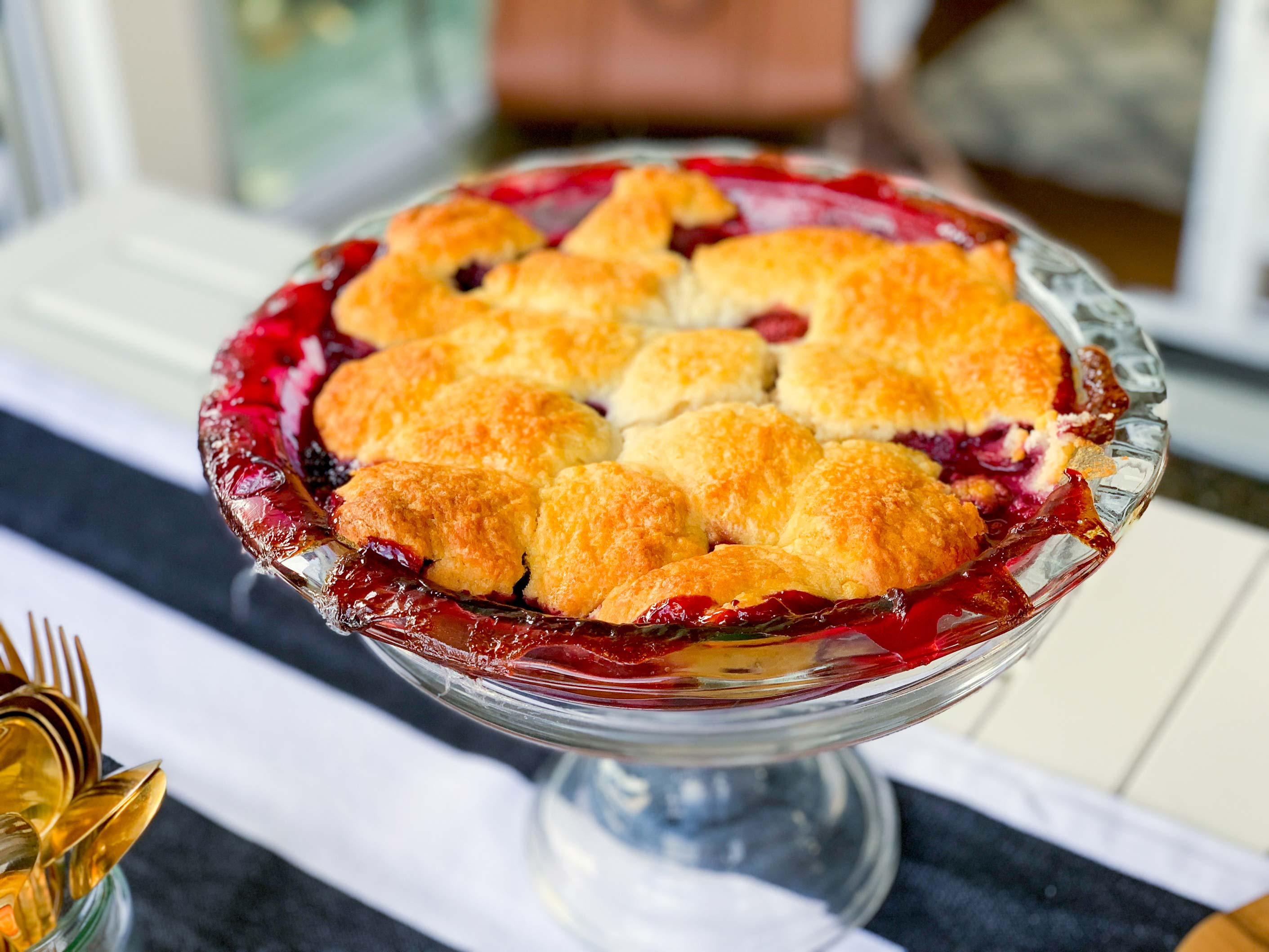 mixed berry cobbler, resting on a cake stand, ready for serving