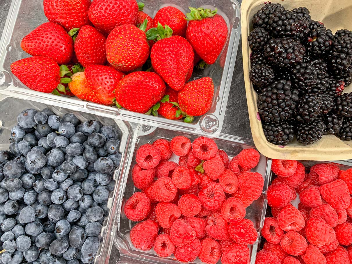containers of strawberries, blackberries, blueberries and raspberries on the counter