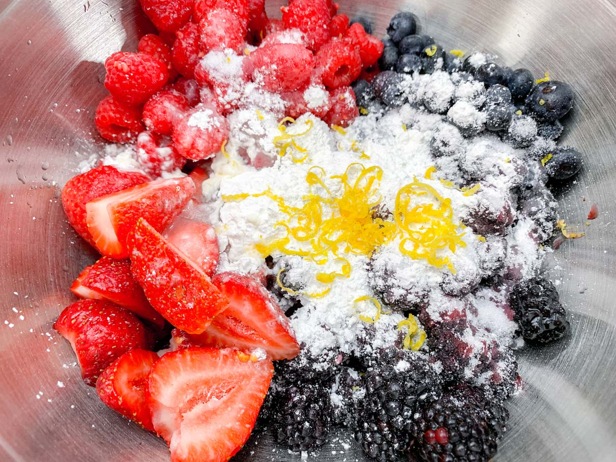 mixed berries with sugar, cornstarch, lemon zest and lemon juice sprinkled on top
