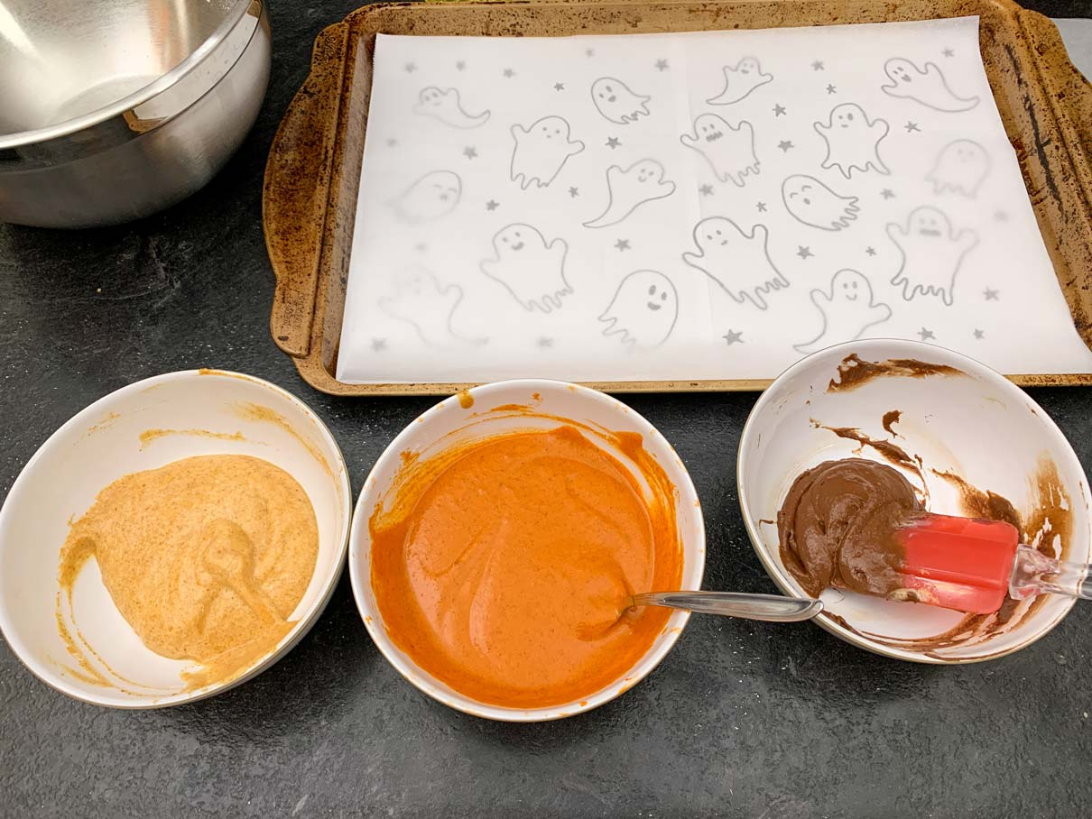 bowl of plain batter, orange batter and black batter all lined up on the counter