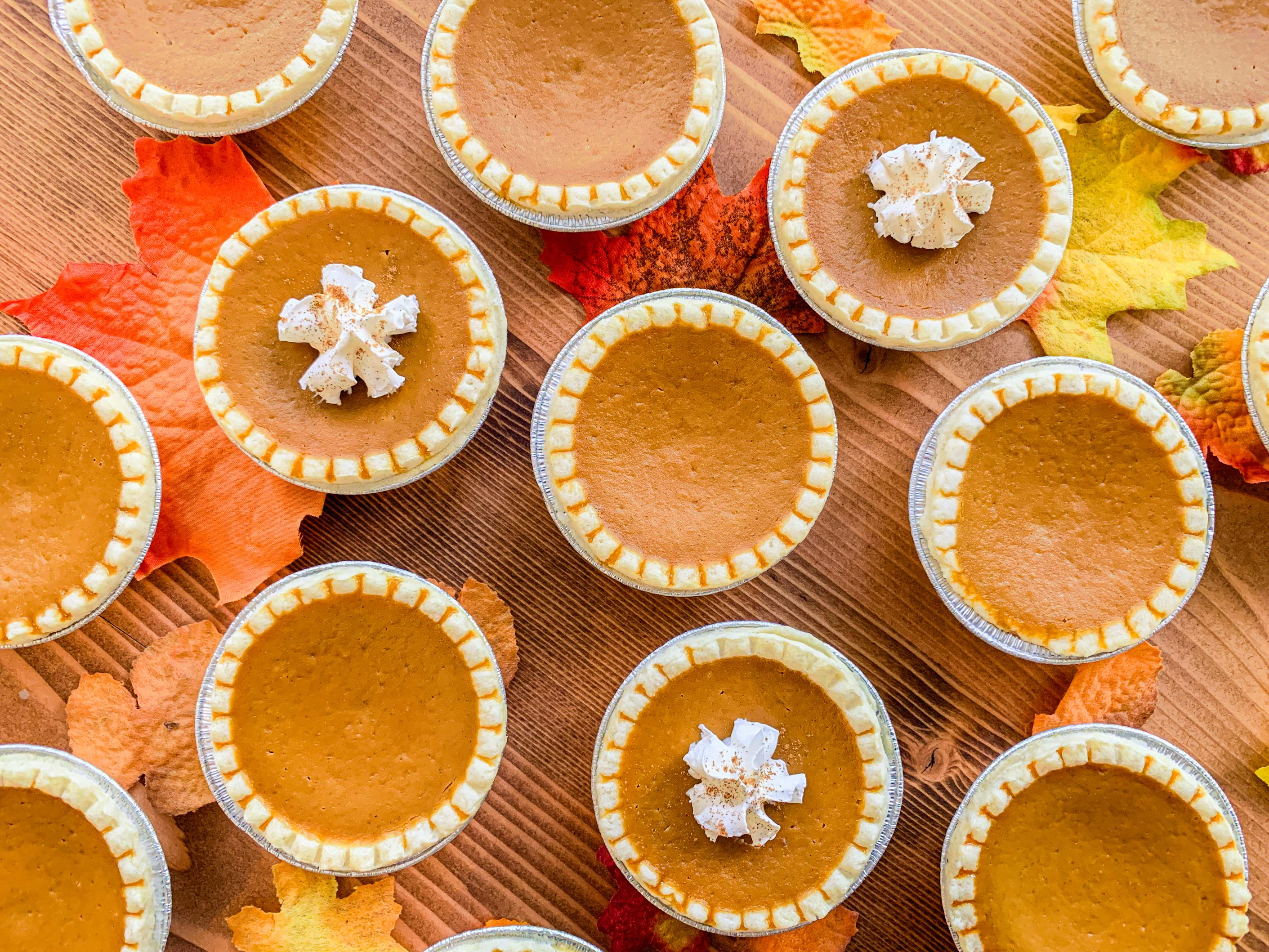 overhead shot of mini pumpkin pies, topped with whipped cream and cinnamon, on wood table top, surrounded by fall leaves